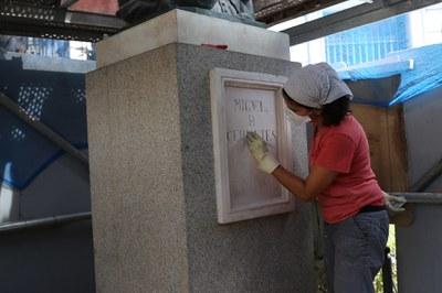 Una restauradora de la empresa contratada para estas intervenciones en monumentos, limpia el pedestal de la estatua de Miguel de Cervantes