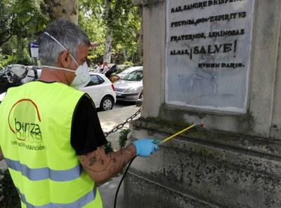 Un operario de la empresa restauradora realiza trabajos de limpieza en el monumento a la Raza, junto al Parque de María Luisa