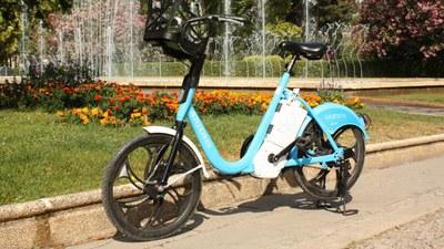 Imagen de una bicicleta eléctrica aparcada a la entrada de una zona verde